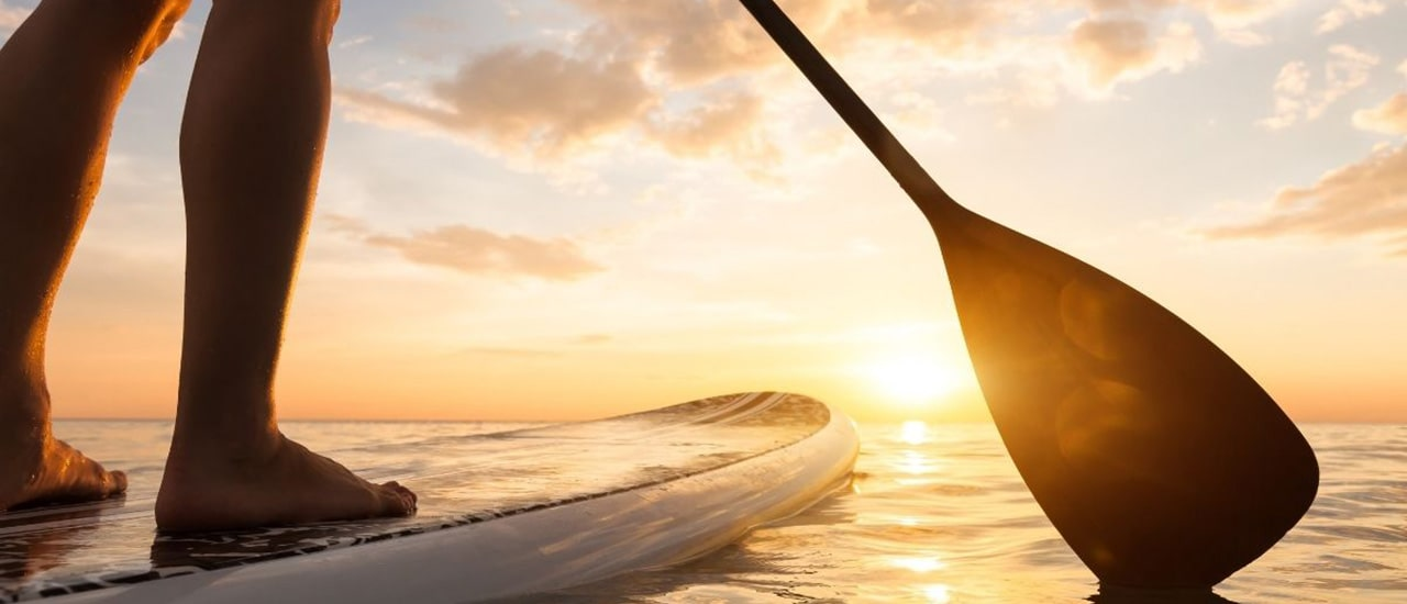 woman on paddleboard with sunset over longboat key