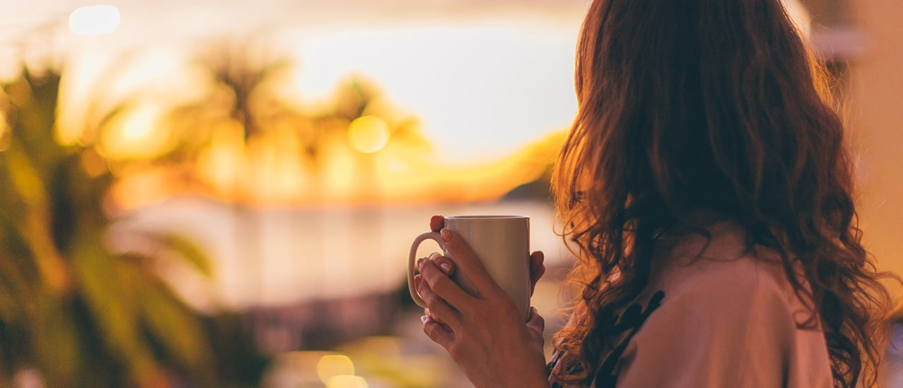 woman holding coffee looking out to longboat key sunset